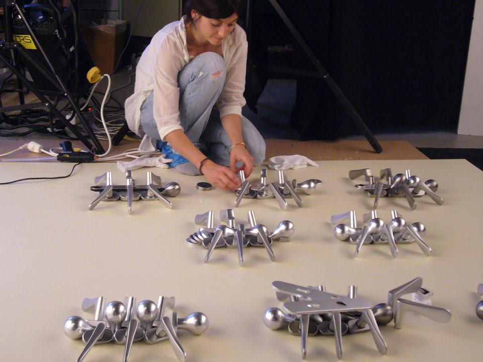 Ein Foto der Künstlerin Sarah Illenberger, wie sie gerade eine Komposition aus Türklinken auf dem Boden erstellt. Das Motiv: Käfer
