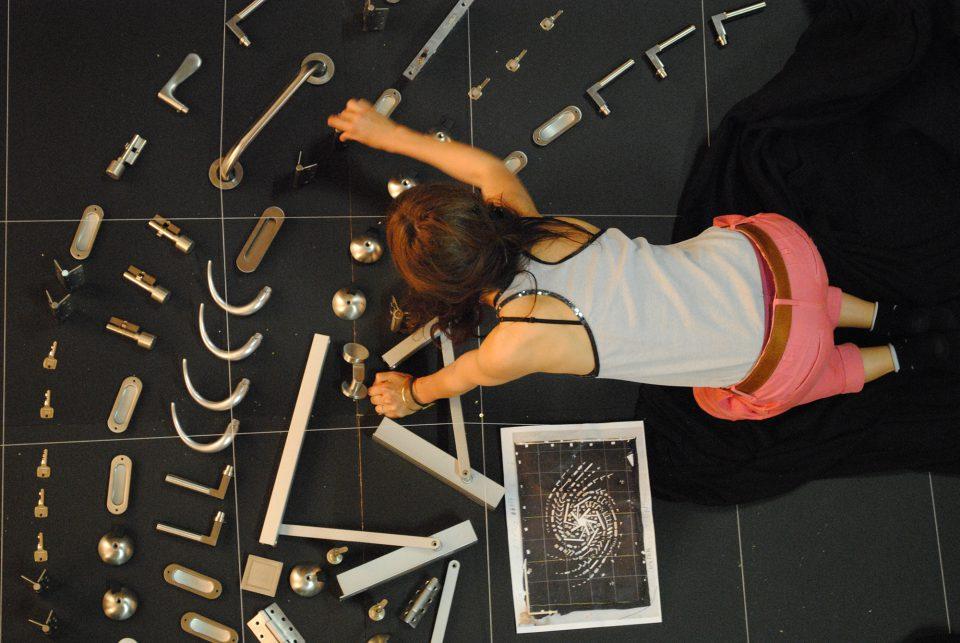 Ein Foto der Künstlerin Sarah Illenberger, wie sie gerade ein Motiv aus Türklinken auf dem Boden zusammenstellt.