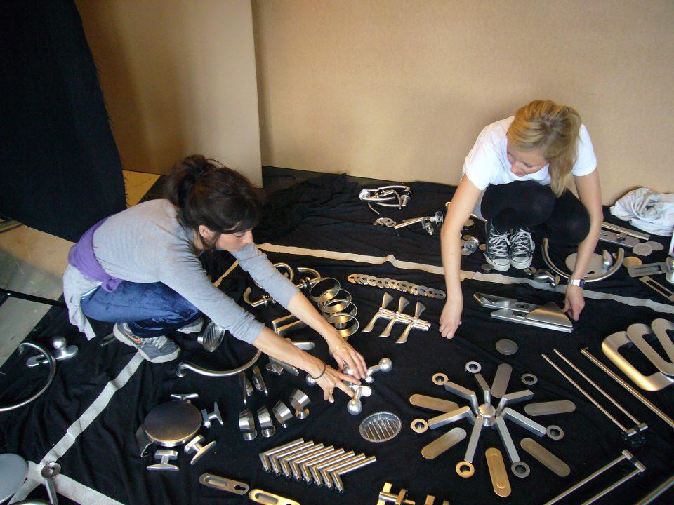 Ein Foto der Künstlerin Sarah Illenberger, wie sie ein Motiv aus Türklinken auf dem Boden zusammenstellt.