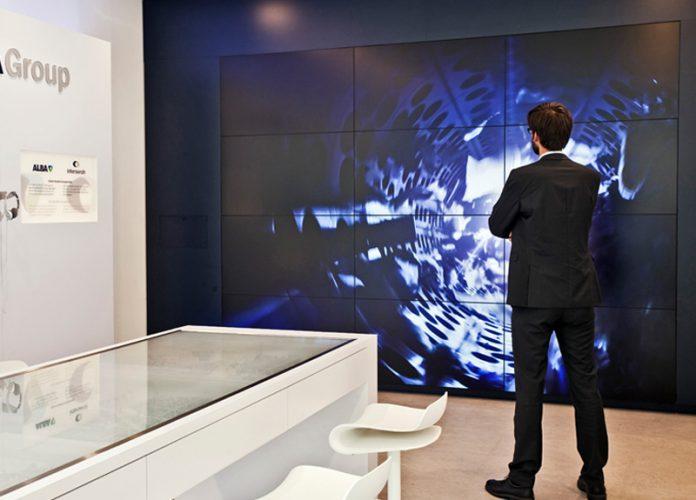 Mann vor einem Riesenbildschirm im Alba Showroom in der Knesebeckstraße in Berlin. Inszenierung der Marke im Raum von der Agentur Realgestalt