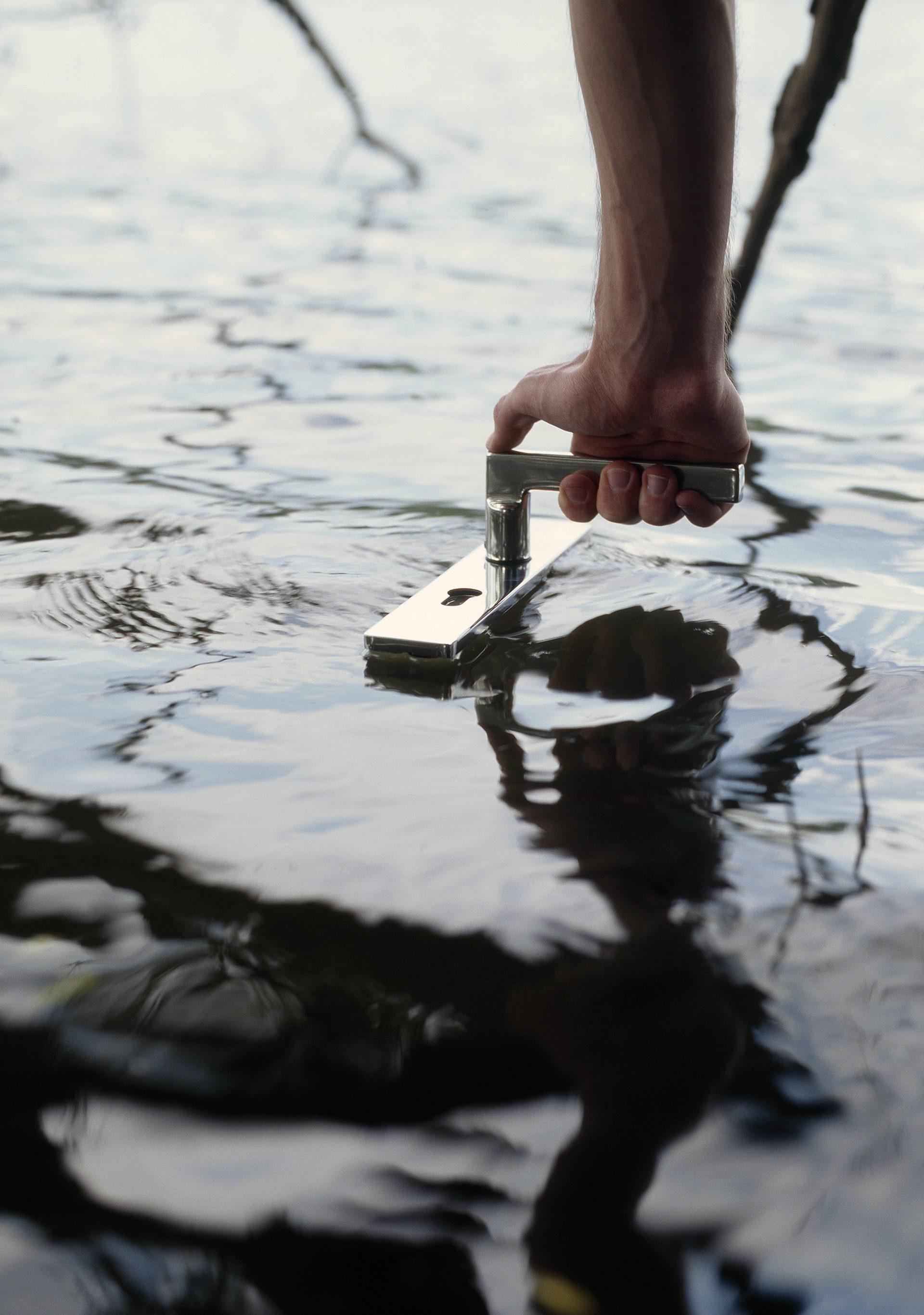 Ein Foto von Fotograf Sascha Weidner, wo eine Hand eine Türklinke greift, die im Wasser schwimmt.